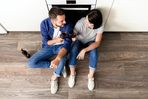 Direttamente sopra la vista della bella coppia positiva in jeans che si siede sul pavimento in parquet in cucina e che beve vino rosso per l'anniversario