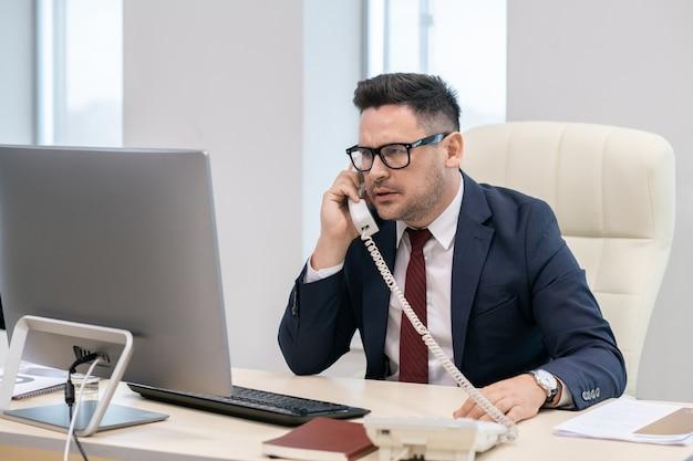 Direttore di azienda contemporanea che parla al telefono