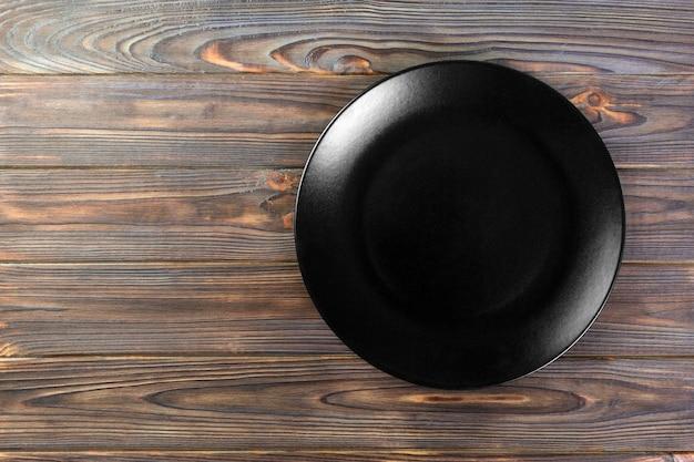 Direttamente sopra il piatto nero opaco vuoto per la cena su una superficie di legno con lo spazio della copia