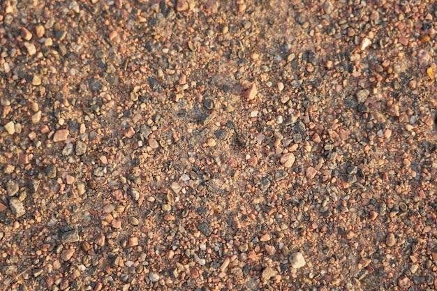 Strada sterrata fatta di piccole pietre di granito come sfondo.