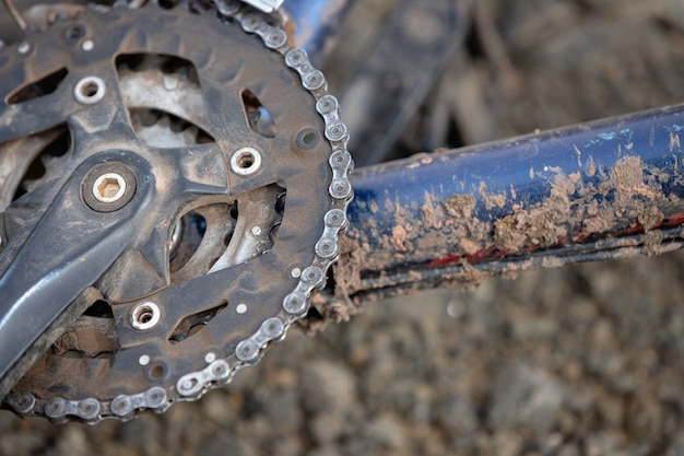 Catena della bici sporca. parte dei pedali e del telaio della bicicletta sono sporchi di sporco.