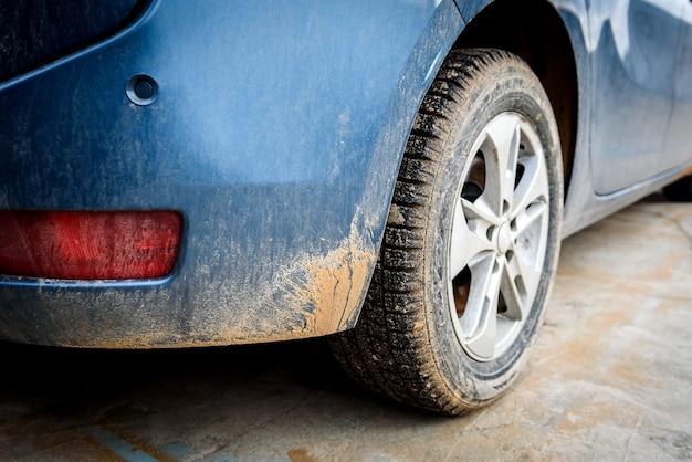 Ruota di automobile sporca con spruzzo di palude sull'auto.