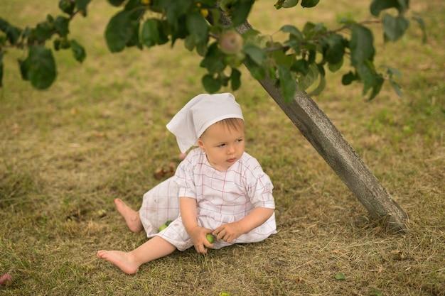 Un bambino sporco si siede sotto un melo.