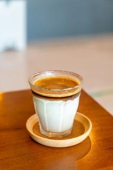 Caffè sporco - un bicchiere di caffè espresso mescolato con latte fresco freddo nella caffetteria e nel ristorante