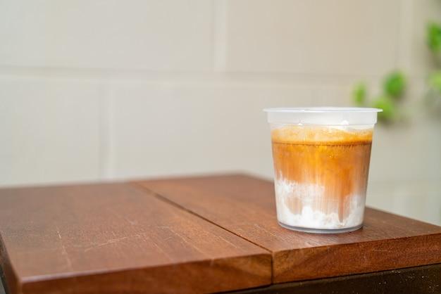 Caffè sporco in un bicchiere da asporto sul tavolo di legno