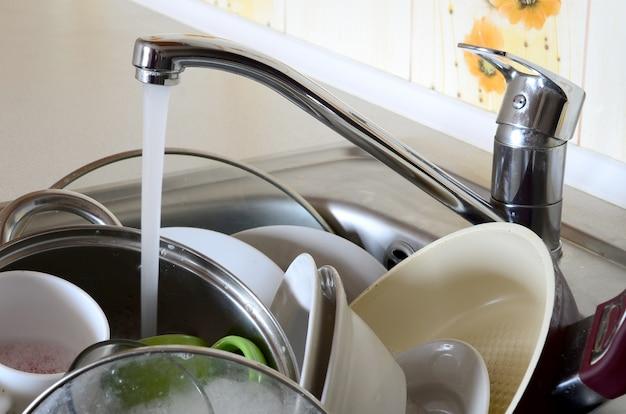 Piatti sporchi e apparecchi da cucina non lavati giacciono in acqua schiumogena
