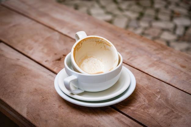 Tazze di caffè bianche vuote sporche sui piattini su un fondo di legno