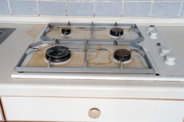Fornello a gas sporco macchie di olio da cucina sul fornello a gas in cucina una cucina sporca e sporca usata per cucinare...