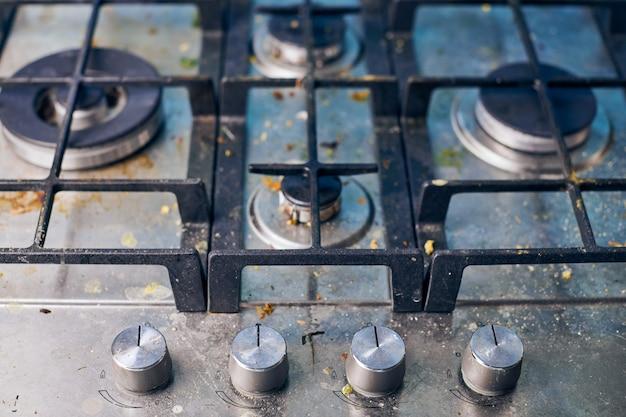 Piano cottura a gas sporco con avanzi di cibo. piano cottura da cucina in acciaio sporco con macchie di grasso. pulizie di primavera, rimuovi macchie di grasso della cucina, macchie di frittura, schizzi d'olio e pezzi bruciati