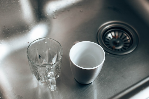 Bicchieri sporchi di vetro e ceramica nel lavandino che lavano i piatti