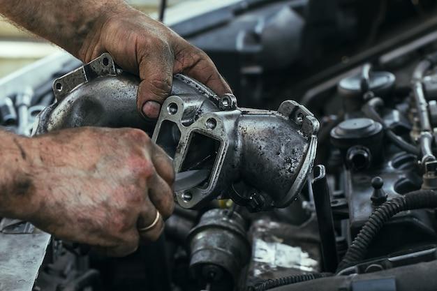 Mani sporche e unte di un uomo che ripara il motore, valvola egr, primo piano.