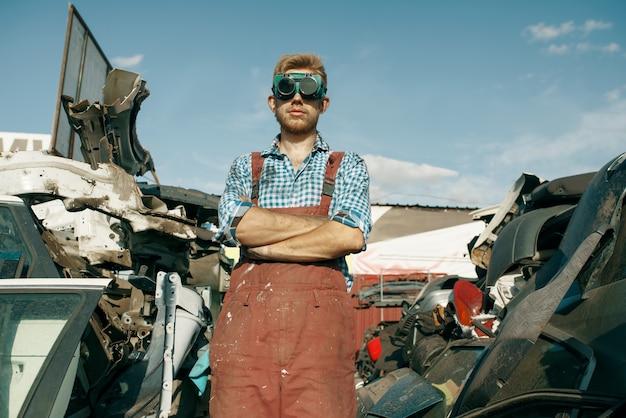 Riparatore maschio sporco in vetri di saldatura sulla discarica di auto. rottami di automobili, cianfrusaglie di veicoli, rifiuti di automobili. trasporti abbandonati, danneggiati e frantumati, cantiere di demolizione