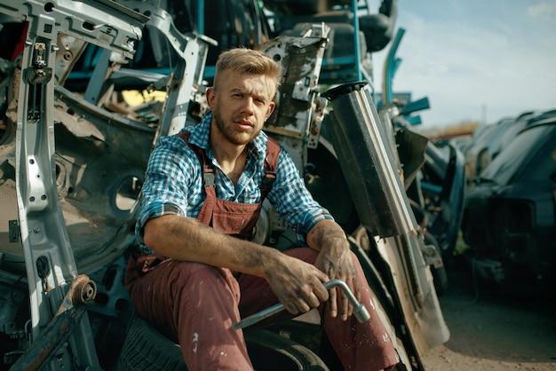Riparatore maschio sporco con la chiave sulla discarica di auto. rottami di auto, spazzatura di veicoli, rifiuti di automobili, trasporti danneggiati e frantumati