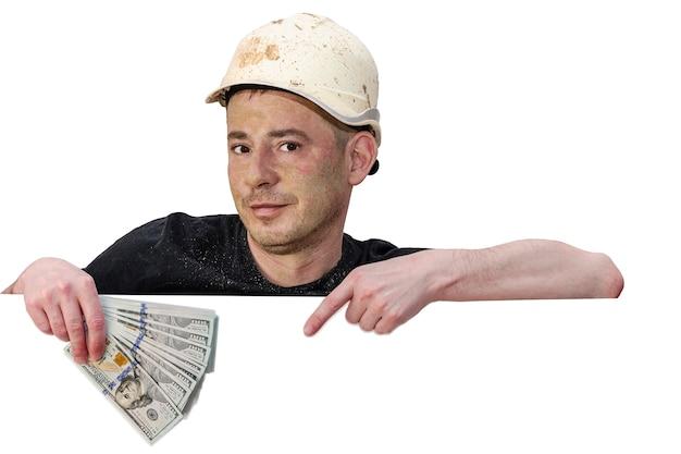 Un uomo sporco con un casco da cantiere tiene in mano dei dollari. il dito indice indica la posizione del testo. sfondo bianco isolato. modello. copia spazio.