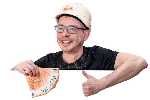 Un uomo sporco con un casco da cantiere tiene in mano banconote in euro. il pollice è sollevato verso l'alto. sfondo bianco isolato. spazio libero per il testo. modello.