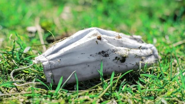 La maschera medica sporca è sdraiata sull'erba