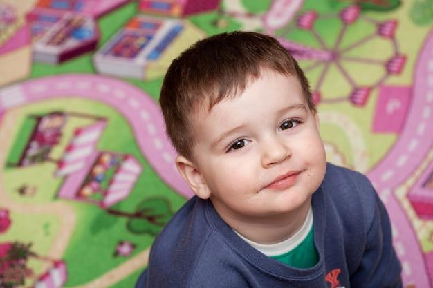 Bocca sporca di un ragazzino bambino seduto sul terreno di gioco e sorridente