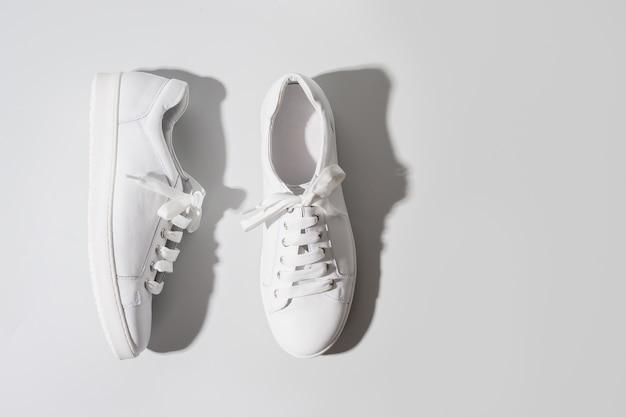 Vecchie scarpe da ginnastica bianche sporche per pulirle sull'azzurro.