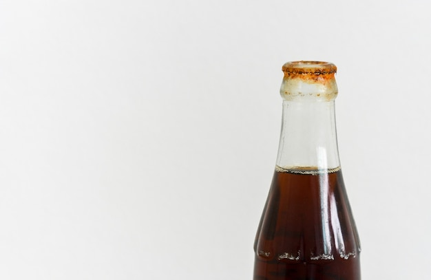 Ruggine sporca intorno alla bocca della bottiglia di vetro della bibita su fondo bianco