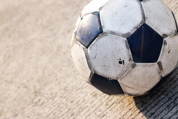 Pallone da calcio sporco isolato sulla strada cementata