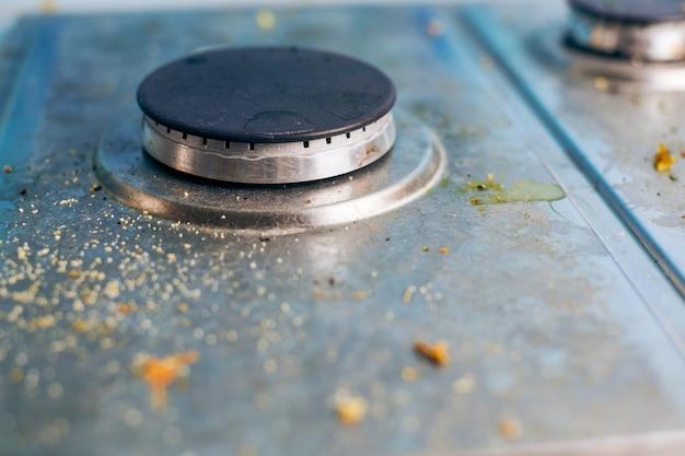 Piano cottura sporco con schizzi di olio, macchie di grasso e avanzi di cibo. piano cottura da cucina in acciaio sporco con macchie di grasso. pulizie di primavera, rimozione di vecchie macchie di cucina, macchie di frittura, briciole e parti bruciate