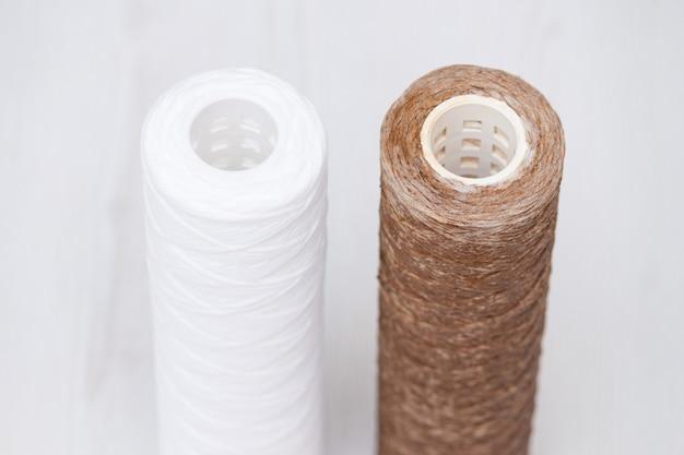 Cartuccia filtro acqua sporca utilizzata e nuovo filtro pulito. sistema di osmosi dell'acqua per uso domestico in cucina.