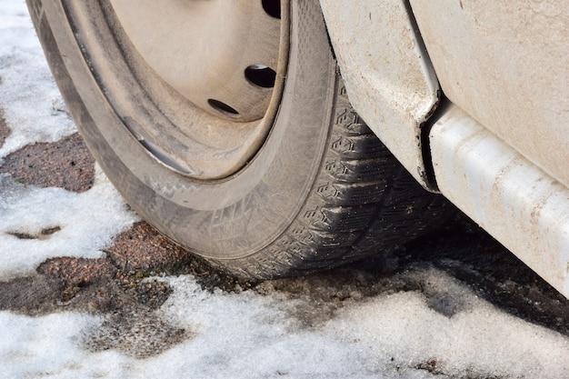Ruota sporca di un'autovettura sul primo piano innevato dell'asfalto