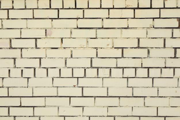 Muro di mattoni bianco sporco con calcestruzzo grigio scuro negli spazi vuoti
