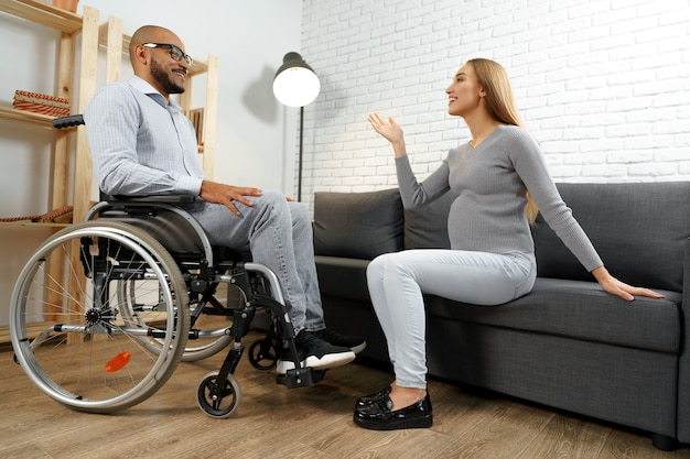 Uomo afroamericano disabile in sedia a rotelle a parlare con la moglie incinta nel soggiorno