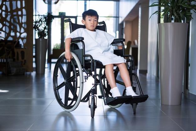 Paziente ragazzo disabile su sedia a rotelle nel corridoio dell'ospedale