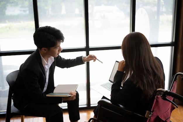 Donna di affari disabile che lavora con il suo collega nel posto di lavoro moderno.