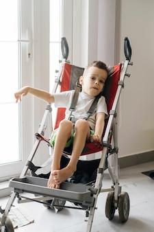 Bambino disabile in passeggino grande accessibilità in carrozzina e passeggino