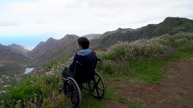 Donna disabile handicappata in sedia a rotelle sulla collina della montagna che gode della vista