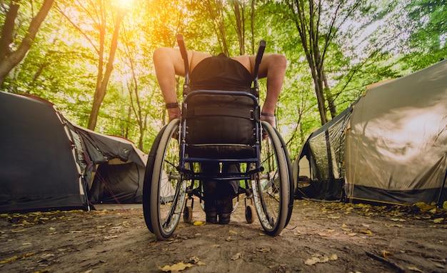 Uomo disabile che riposa in un campeggio con gli amici. sedia a rotelle nella foresta