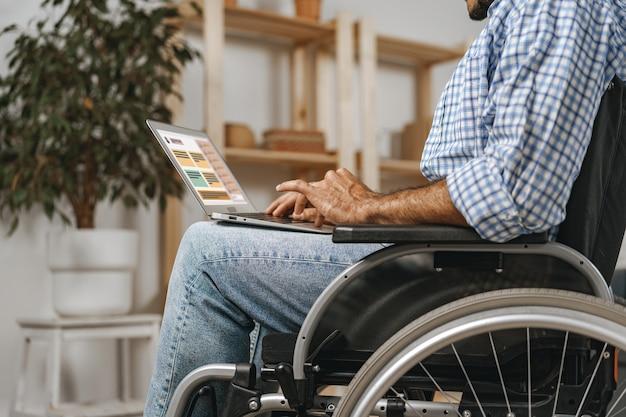 Uomo disabile seduto su una sedia a rotelle e che usa il laptop