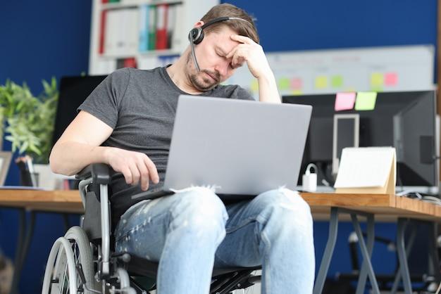 Uomo disabile che dorme in sedia a rotelle con il computer portatile in grembo. resilienza al concetto di lavoro