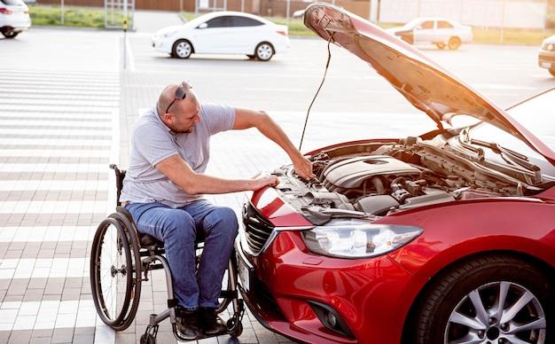 L'uomo disabile in sedia a rotelle controlla il motore della sua auto al parcheggio