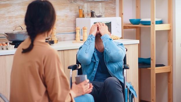 Uomo disabile in sedia a rotelle che ha un conflitto con la moglie in cucina. ragazzo con paralisi handicap disabilità handicappato difficoltà a ottenere aiuto per la mobilità dall'amore e dalla relazione
