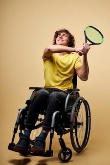Uomo disabile sulla sedia a rotelle che tiene la racchetta per il tennis, il ragazzo riccio caucasico sta giocando a tennis, fondo beige isolato
