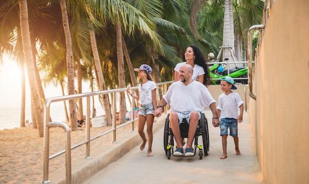 L'uomo disabile in sedia a rotelle si muove su una rampa per la spiaggia con la sua famiglia.