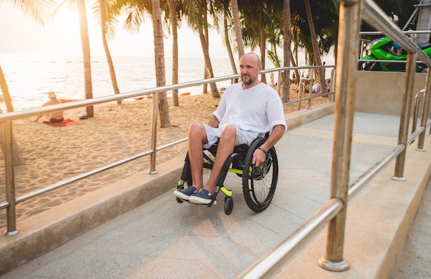L'uomo disabile in sedia a rotelle si muove su una rampa verso la spiaggia.
