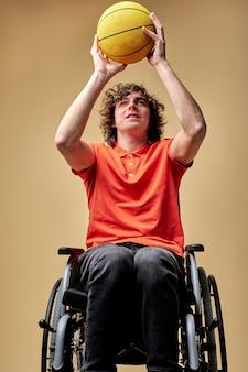 Uomo disabile in sedia a rotelle treno con palla da basket, atleta caucasico che si esercita, nonostante la disabilità