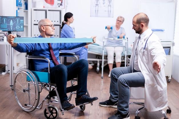Uomo disabile in sedia a rotelle che allena la forza muscolare con la fascia elastica nell'ospedale di recupero