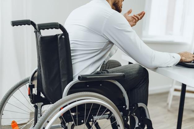 Uomo disabile in sedia a rotelle utilizzando laptop da vicino