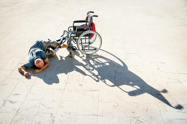 Uomo disabile con handicap che ha un incidente con la sedia a rotelle
