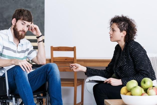 Uomo disabile con giovane psicoterapeuta