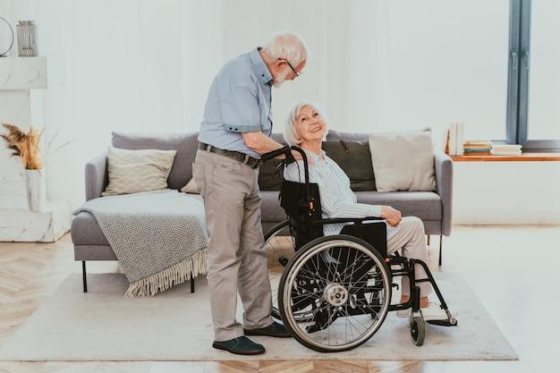 Disabile vecchio su sedia a rotelle coppia senior a casa partner di ritorno dall'ospedale