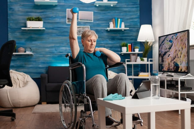 Anziana disabile in sedia a rotelle che alza il braccio che allena la resistenza muscolare utilizzando il recupero dei manubri dopo la disabilità muscolare guardando video cardio sul laptop