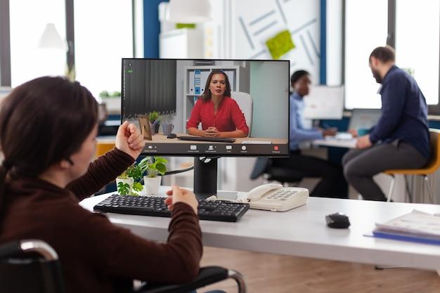 Imprenditrice paralizzata disabile in sedia a rotelle che parla con il manager remoto durante la presentazione della società di pianificazione della conferenza di videochiamata online nell'ufficio aziendale di avvio. teleconferenza sullo schermo