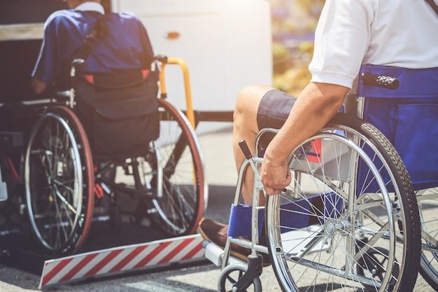 Disabili che si siedono sulla sedia a rotelle e che vanno al bus pubblico